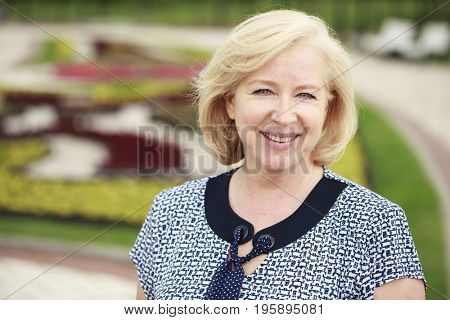 Portrait of lovely middle aged blonde woman in the summer park