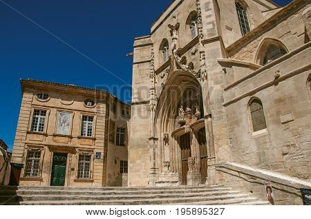 Building and front facade of church in the city center of Avignon, under a sunny blue sky. Located in the Vaucluse department, Provence-Alpes-Côte d'Azur region, southeastern France