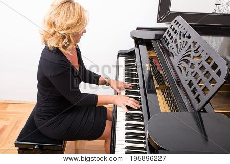 Hands of an elegant classical musician woman playing on piano.