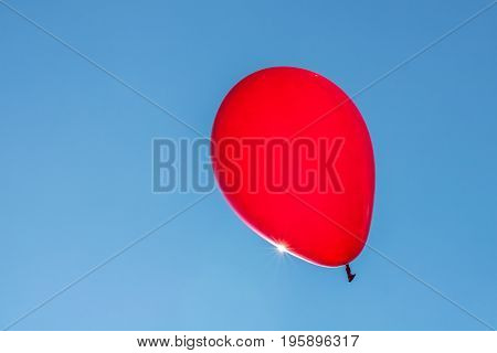 Horizontal photo of a bright red balloon against a blue sky and the sun gleaming off the edge of the balloon