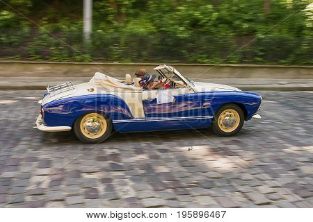 Lviv Ukraine - June 4 2017: Old retro car Volkswagen Karmann Chia with its owner and au unknown passenger taking participation in race Leopolis grand prix 2017 Ukraine.