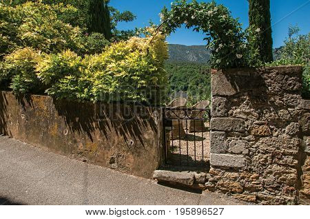 View of small garden behind iron gate and stone wall in the village of Ménerbes. Located in the Vaucluse department, Provence-Alpes-Côte d'Azur region, southeastern France