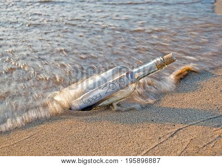 New Year 2018 message in a bottle on the beach with splashing water
