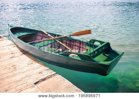 green wooden fishing boat on clear water near the pier