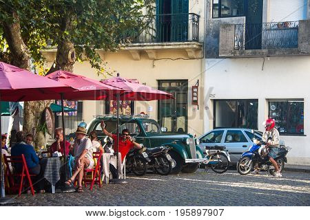 Colonia del Sacramento Uruguay - April 5 2013: Tourists enjoy a sunny autumn day in a street cafe in the historic center of one of the oldest towns in Uruguay