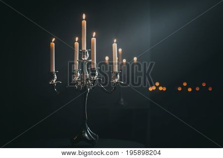 Vintage candlestick with candles in darknes and light