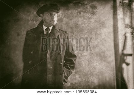 Retro 1920S English Gangster Smoking Cigarette. Wearing Black Coat And Flat Cap.