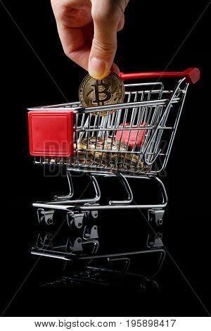 hand throws a bitcoin into trolley.