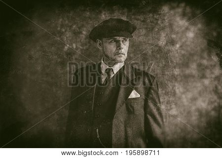Retro 1920S English Gangster Wearing Flat Cap And Suit.