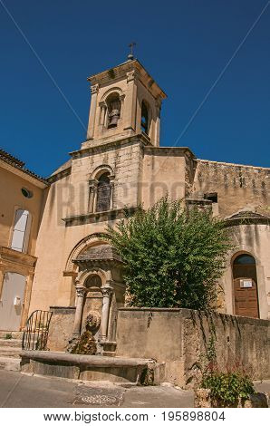 Close-up of church with steeple and flowers, in the historical village of Lourmarin. Located in the Vaucluse department, Provence-Alpes-Côte d'Azur region, southeastern France