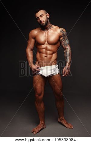 Sexy closeup portrait of handsome topless male model with beautiful eyes. Sexy man or muscular macho, bodybuilder, with muscle torso, body with six packs and abs poses on black background in white panties. poster