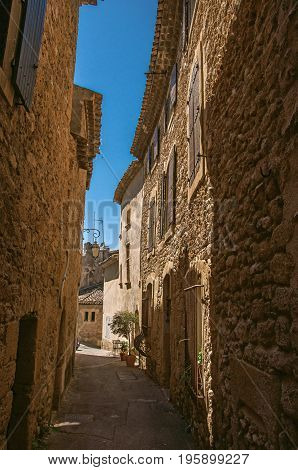 View of typical stone houses with sunny blue sky, in a narrow alley of the historical village of Lourmarin. In the Vaucluse department, Provence-Alpes-Côte d'Azur region, southeastern France