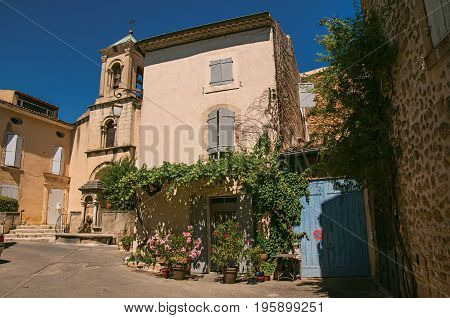 View of house with flowers and church with steeple, in front of a square of the historical village of Lourmarin. Located in Vaucluse department, Provence-Alpes-Côte d'Azur region, southeastern France