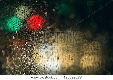 Seasonal scene Rain drops on window glasses with bokeh background selective focus on raindrops foreground and blur city lighting at night. romantic background lowkey lighting and effect filter.