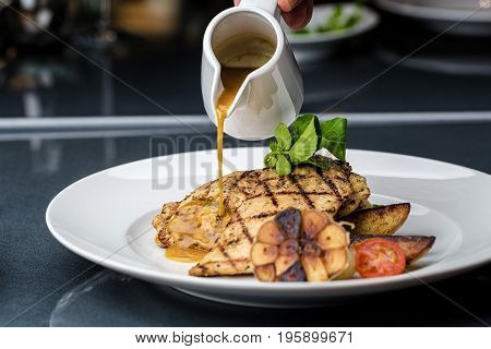 Grilled chicken fillet served with french fries, asparagus and cherry tomatoes, decorated with grilled garlic and baby spinach