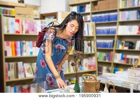 Asian Girl Choosing Book In A Bookstore