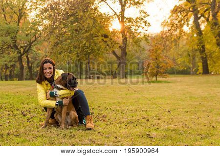 Beautiful young woman with her Dog in the Park in the autumn.