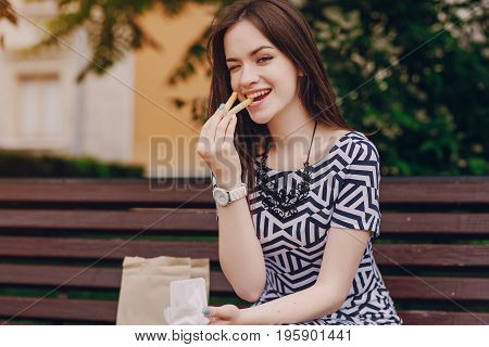 young model enjoying the break and eating fries