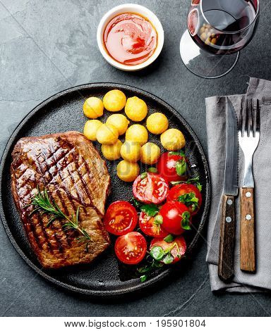 Grilled Beef Steak Served On Cast Iron Plate With Tomato Salad, Potatoes Balls And Red Wine. Barbecu