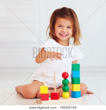 Cute Little Baby Girl Playing With Wooden Toy On The Floor
