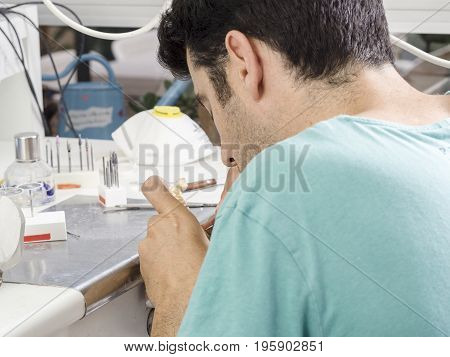 Dental Technician Modelling An Implant Ceramic Tooth With A Drill
