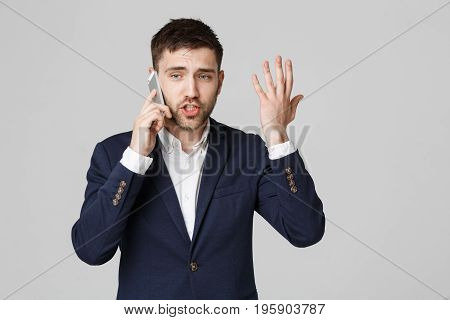 Business Concept - Portrait young handsome angry business man in suit talking on phone looking at camera. White background.