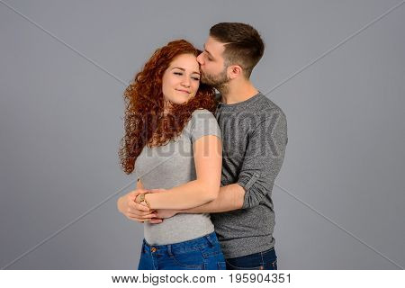 A beautiful young couple hugging and kissing each other in the studio