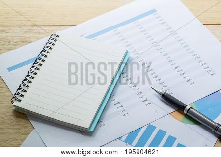 Financial Charts And Business Graphs, Note And Pen On The Table