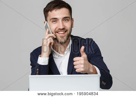 Business Concept - Portrait Handsome Business man showing thump up and smiling confident face in front of his laptop. White Background.Copy Space.