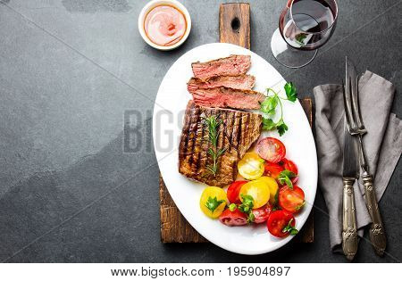 Sliced Medium Rare Grilled Beef Steak Served On White Plate With Tomato Salad And Potatoes Balls. Ba