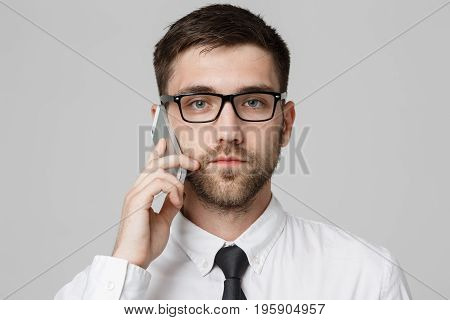 Lifestyle and Business Concept - Portrait of a handsome businessman serious talking with mobile phone. Isolated White background. Copy Space.