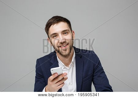 Business Concept - Portrait handsome happy handsome business man in suit playing moblie phone and smiling with laptop at work office. White Background.