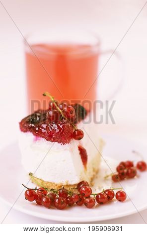 Slice of cheesecake on a plate with branches of red currant and in blurring on a background of a mug of fruit drink