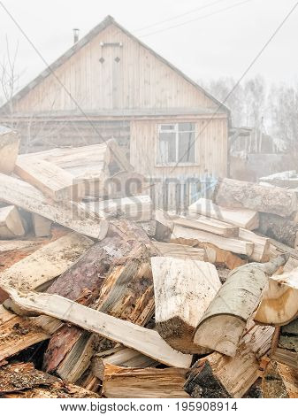 Rural landscape with a pile of pine and aspen logs on the background of the bath-house in the foggy dank autumn day