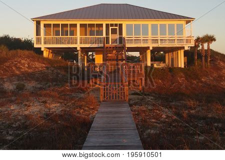 House and walkway on the beach at sunrise