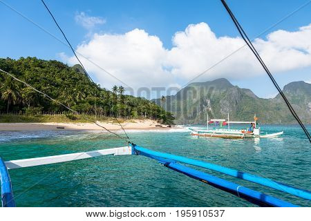 EL NIDO, PALAWAN, PHILIPPINES - JANUARY 19, 2017: Traditional boat, beautiful beach, tropical weather in El Nido, Palawan.