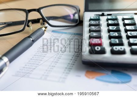 Financial Charts On The Table With Laptop, Calculator, Pen And Glasses Business Concept