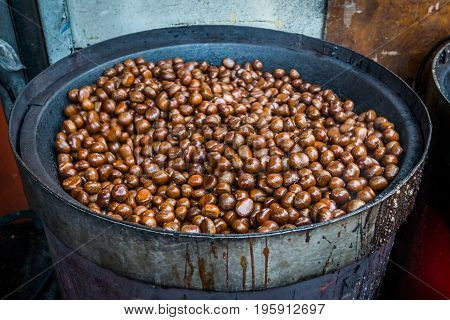 Roasting chestnuts with traditional machinery in Chinatown.