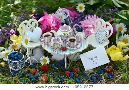 Small dishware with vintage objects, note with text love you, berries and flowers. Mad tea party concept. Beautiful greeting card with summer flowers and vintage objects. Fairies in the garden