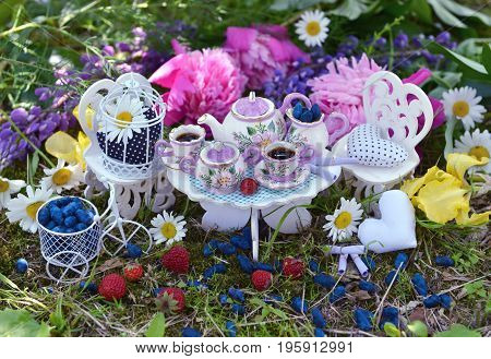 Cute furniture with small dishware, vintage objects, berries and flowers in the garden. Mad tea party concept. Beautiful greeting card with summer flowers and vintage objects. Fairies in the garden