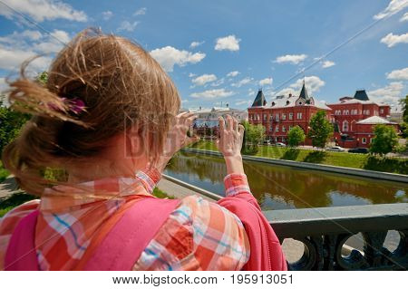 Back view of woman photographing famous palace during excursion. Russia, Orel city orlik embankment state bank building