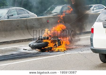 Traffic accident between a car and a motorcycle, after crash the motorcycle has been embraced with fire.