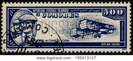 Moscow Russia - July 18 2017: A stamp printed in Comoros shows French aviation pioneers brothers Gabriel and Charles Voisin and their old airplane