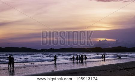 On the beach the sea the evening the sunset so the sky is bright orange people stroll. Watch the sunset Kra-bi evening sea activities in Thailand.