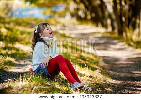 Little laughing happy girl sitting in autumn park