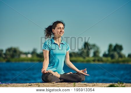Portrait of young happy woman meditating in the lotus position outdoor