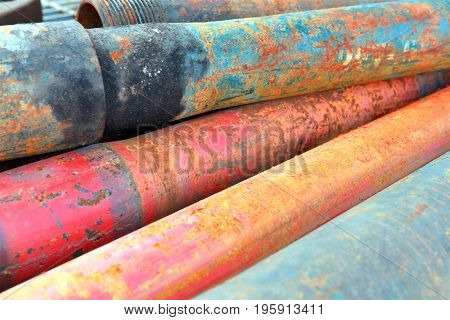 An abstract image of rusted and weathered oil field pipes.
