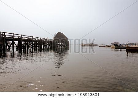 Dock and boats in the harbor as the morning fog slowly fades away
