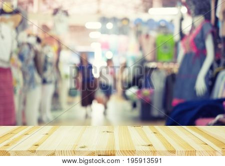 Blurred image of retail store in shopping mall montage with wood table for background.