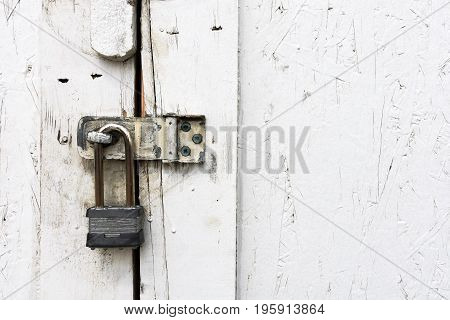 A close up image of an old weathered padlock on a white door.
